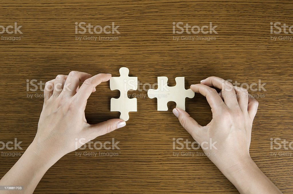 Fitting two jigsaw pieces together royalty-free stock photo