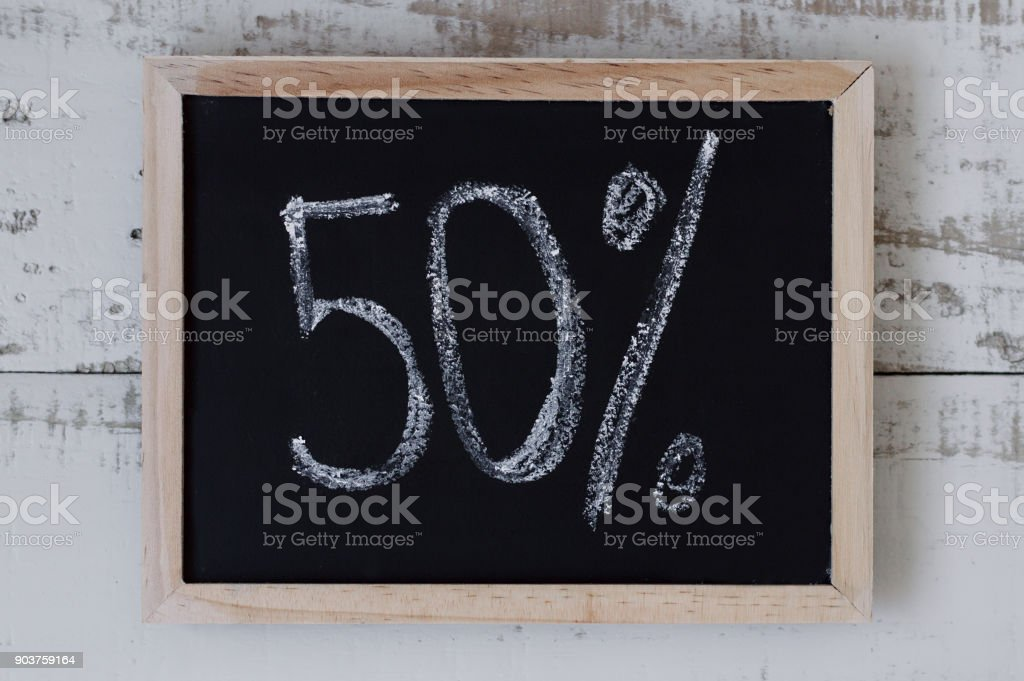 Fity percent. Blackboard with handwritten figures 50%. Black friday sale stock photo
