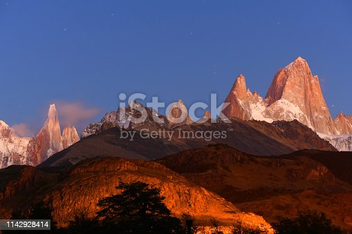 Dawn over Monte Fitz Roy  (11,073 feet /3,375 m) on the right and slim tower of Mt Cerro Torre to the left, spectacular mountains in Patagonia, on the border between Argentina and Chile. Picture taken in April at El Chalten village, just before sunrise, stars are still visible, moved a little during long time exposure.