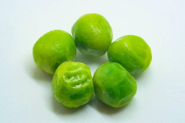 Five 5 green vegan peas macro studio shot stock photo