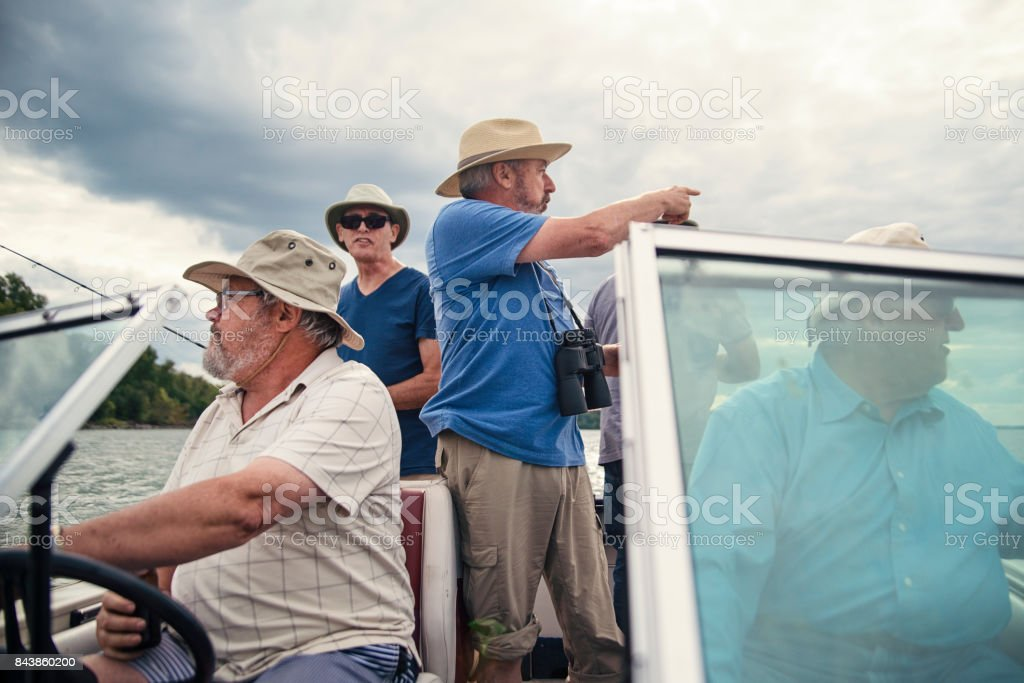 Five active seniors brothers on a fishing trip on a boat. stock photo