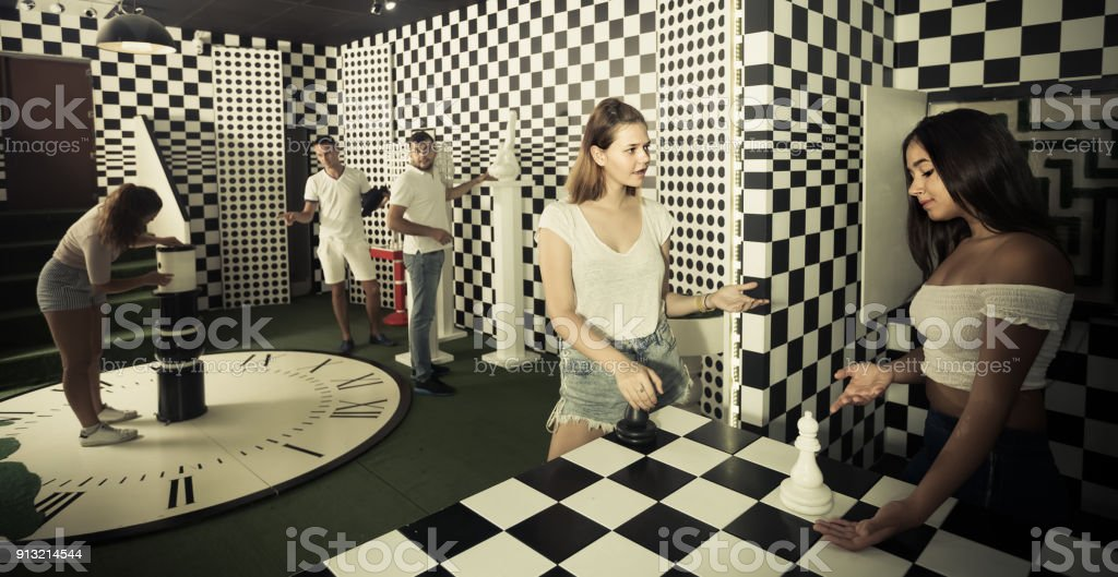 Five adults solving different conundrum in quest room stock photo