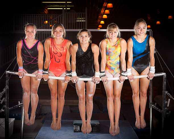 Five Advanced Gymnasts Pose on Uneven Bars stock photo