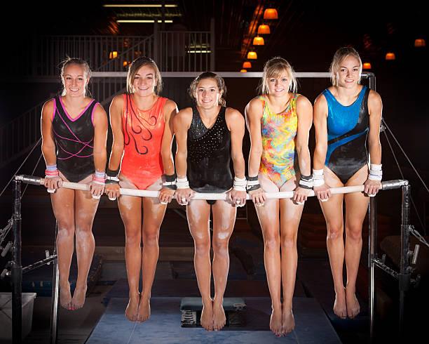 Cinq avancée gymnastes poser sur âpre et Bars - Photo