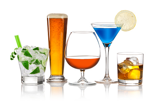 Colorful lineup of popular bar drinks, including caipirinha, brandy, beer, scotch, martini. The drinks are arranged in a row on reflective white background. Visible reflection of the glasses on foreground