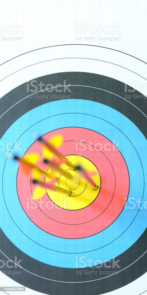 Five arrows in the bull\'s-eye of an archery target. Selective focus...