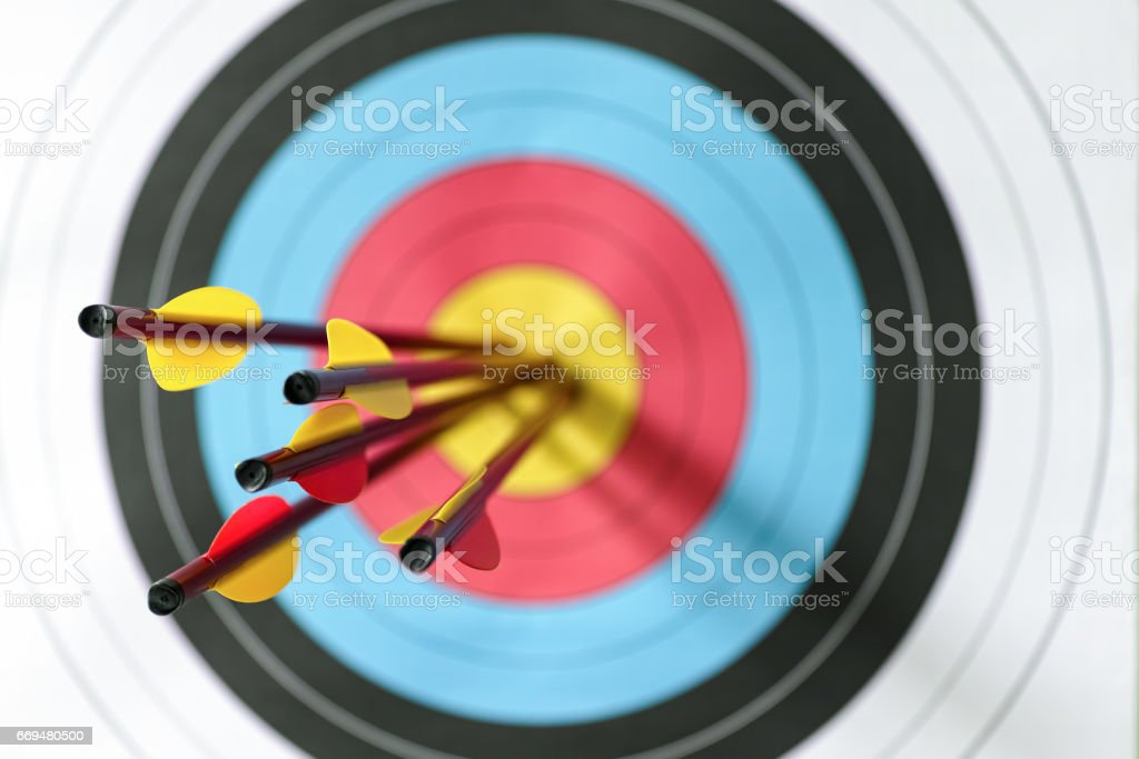 Five arrows in the bull's-eye of a sports target. stock photo