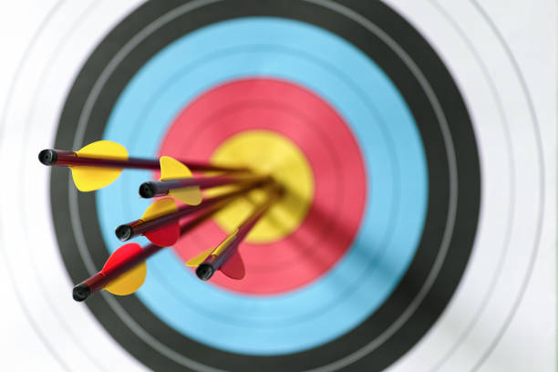 five arrows in the bull's-eye of a sports target. - sports target stock photos and pictures