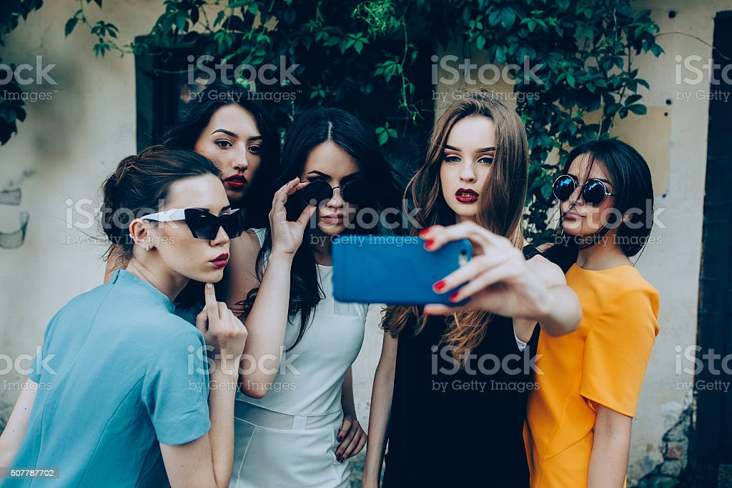 five beautiful young girls five beautiful young girls make selfie on the street near house Adult Stock Photo
