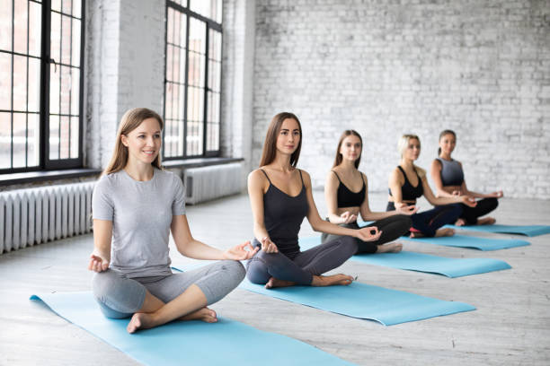 Five beautiful young yoga women sitting cross legged in a lotus pose at a gym. Balance of soul and body. stock photo