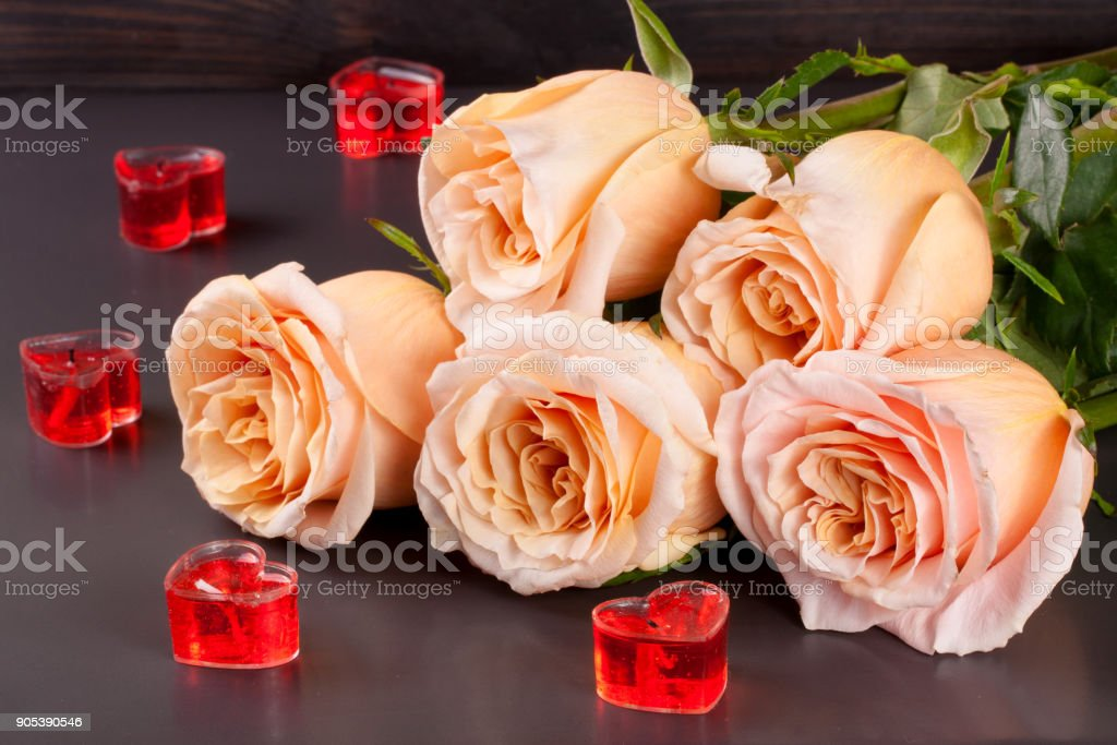 five beige rose with candles in the shape of heart on a dark wooden background stock photo