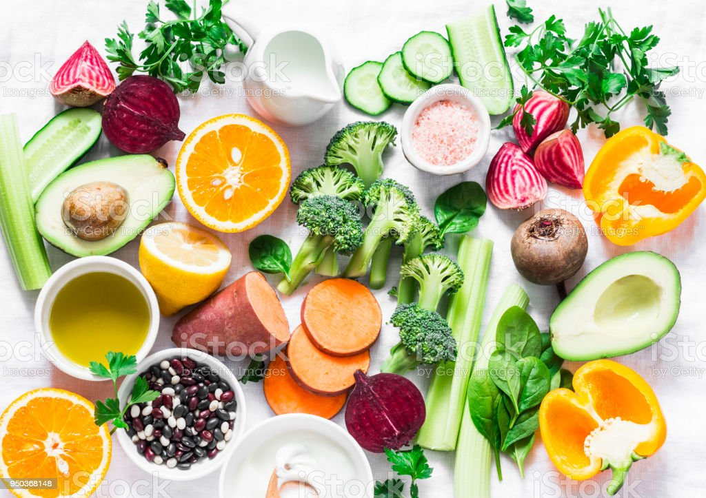 Five best vitamins for beautiful skin. Products with vitamins A, B, C, E, K - broccoli, sweet potatoes, orange, avocado, spinach, peppers, olive oil, dairy, beets, cucumber, beens. Flat lay, top view royalty-free stock photo