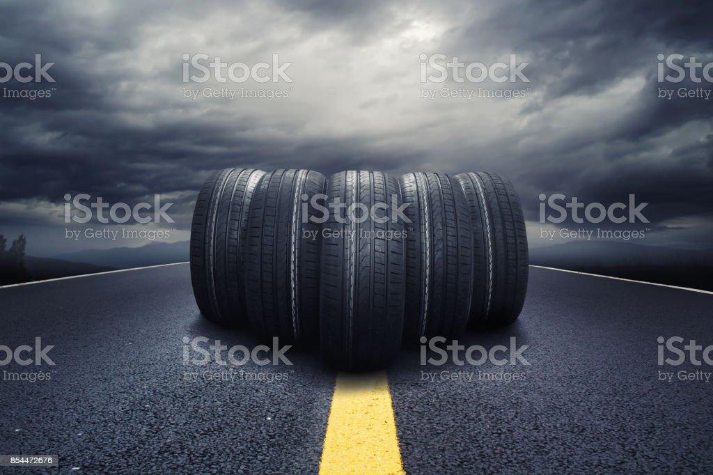 Fünf schwarze Reifen Rollen auf einer Straße mit Wolken – Foto