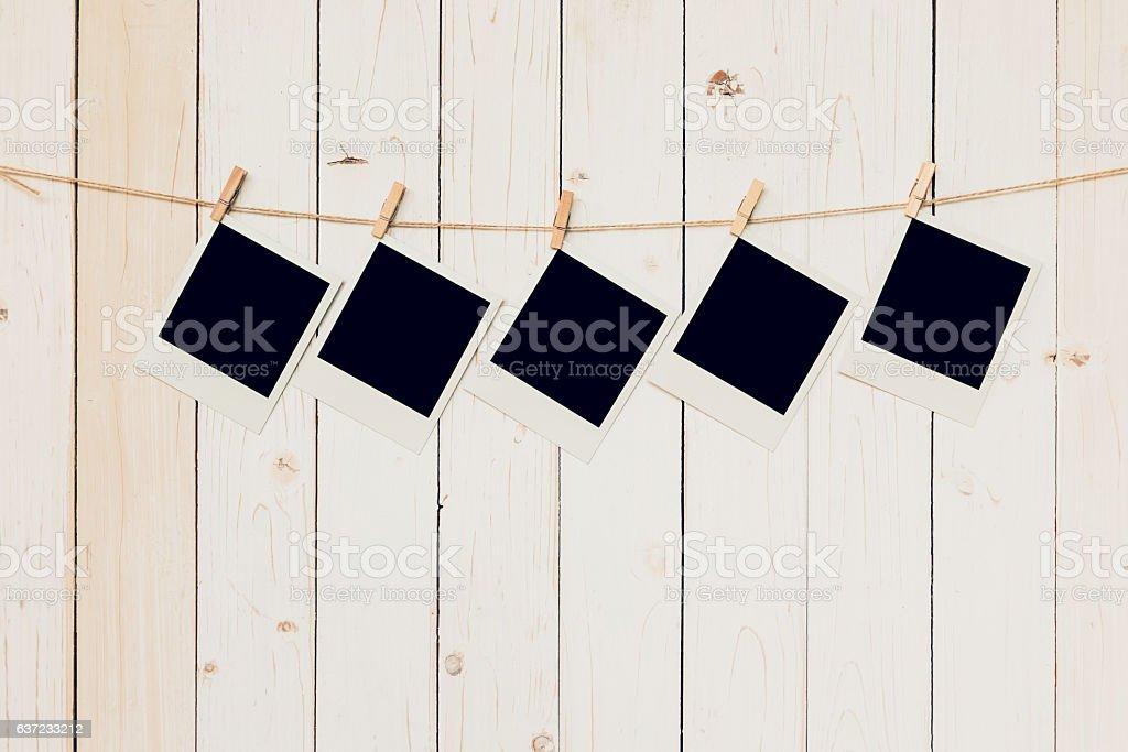 Five (5)blank photo frame hanging on white wood background stock photo