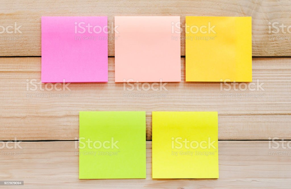 five blank sticky note or post note colorful yellow green and pink on wood table or wood board. stock photo