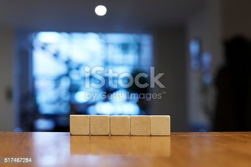 istock Five blank stone blocks on wooden table 517467284
