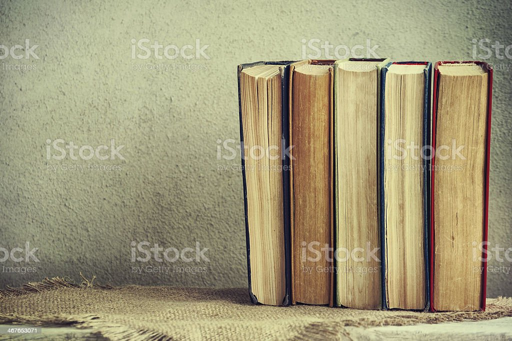 Five books stand neatly on top of table stock photo