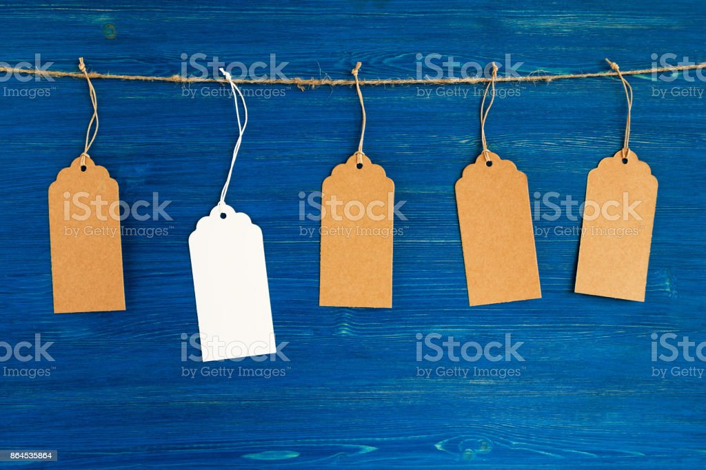 Five brown and white blank paper price tags or labels set hanging on a rope on the blue wooden background. stock photo