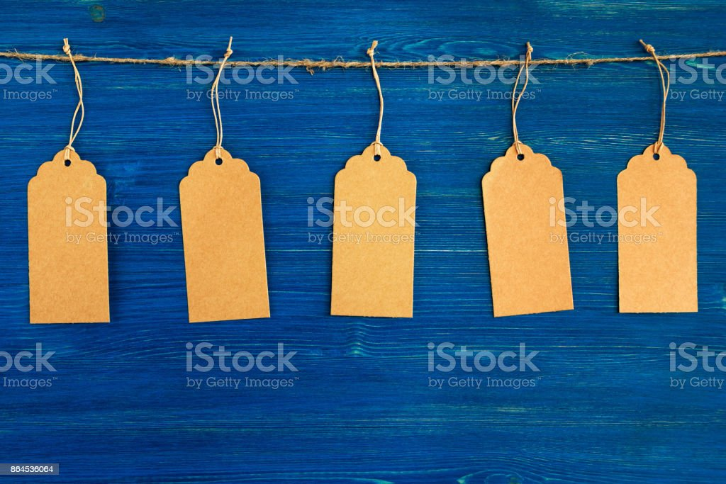 Five brown blank paper price tags or labels set hanging on a rope on the blue wooden background. stock photo