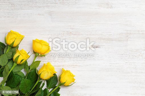 Five buds of yellow roses in the lower left corner on white wooden background