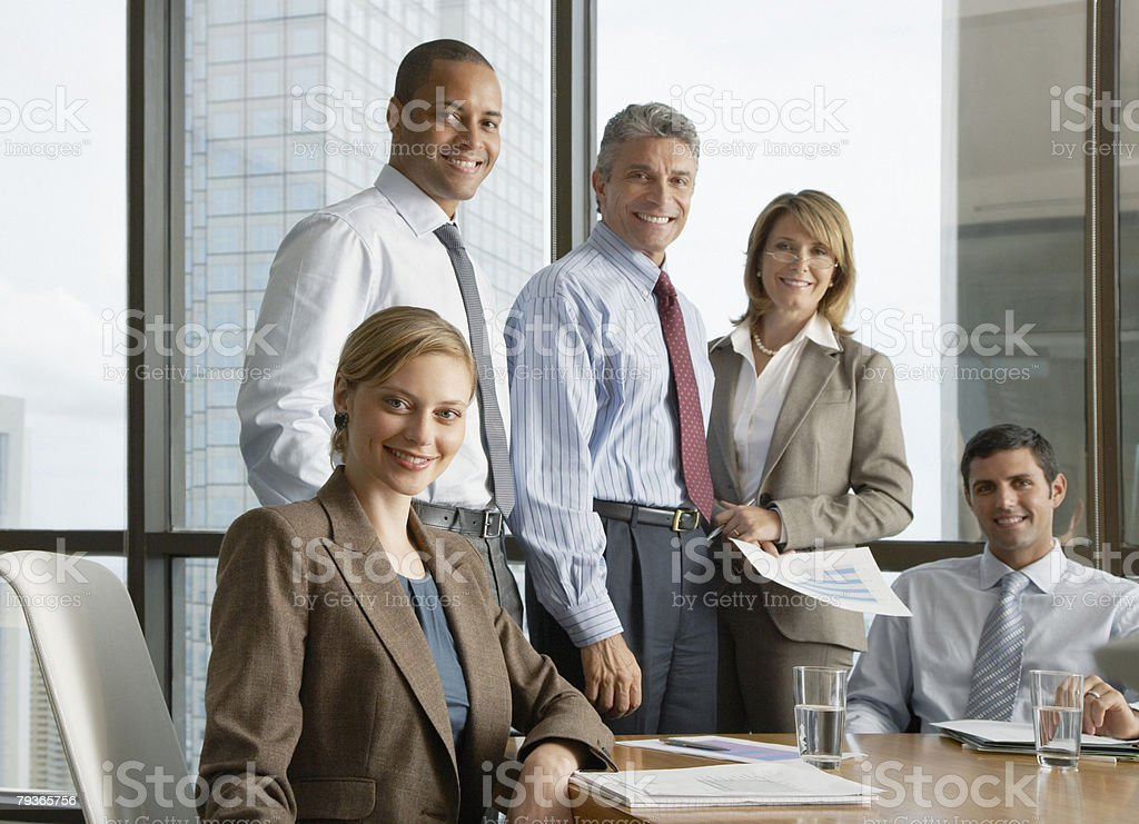 Five businesspeople in a boardroom looking at camera stock photo