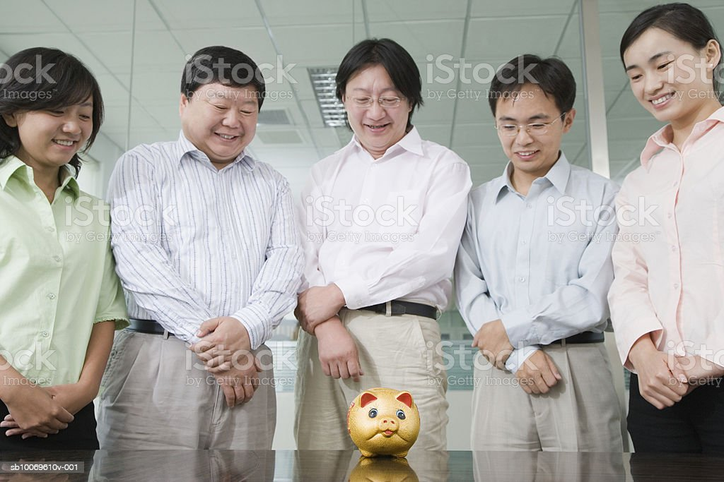 Five businessperson looking at piggy bank on table, smiling royalty-free stock photo