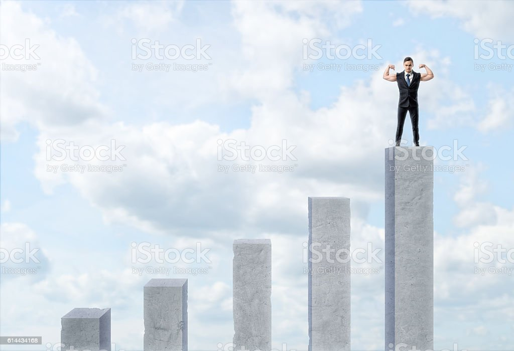 Five cement column with varied length and businessman standing on stock photo
