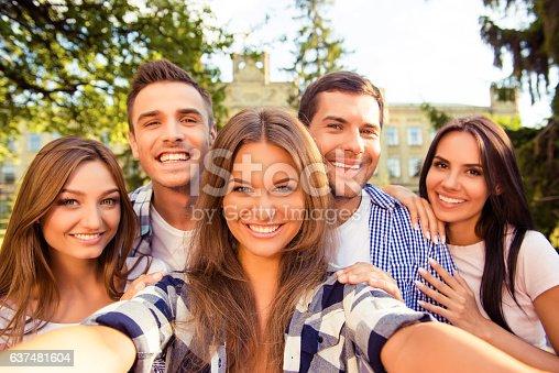 istock five cheerful best friends having fun and making selfie photo 637481604