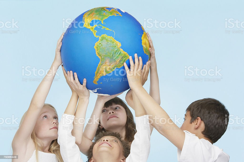 Five children holding up a globe indoors royalty-free stock photo