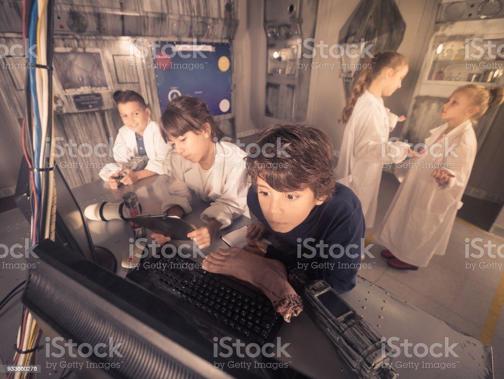 five children solve task in the bunker quest room stock photo
