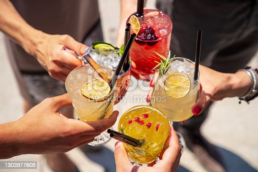 istock Five cocktails in hands joined in celebratory toast 1303977605