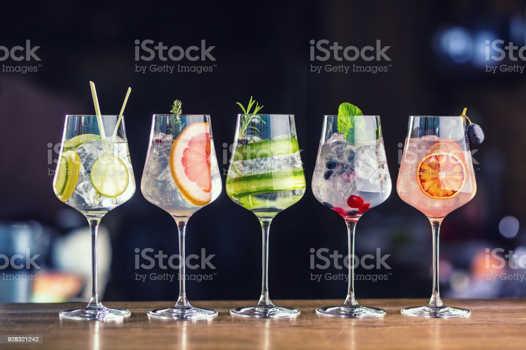 Five colorful gin tonic cocktails in wine glasses on bar counter in pup or restaurant stock photo