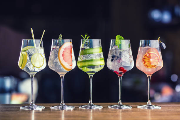 five colorful gin tonic cocktails in wine glasses on bar counter in pup or restaurant - bottle soft drink foto e immagini stock