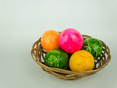 Five coloured Easter eggs in a small woven basket
