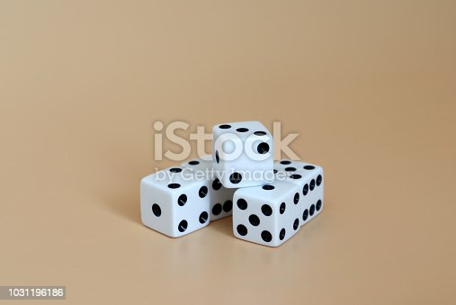 istock Five dice on a soft brown background. 1031196186