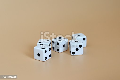 istock Five dice on a soft brown background. 1031196268