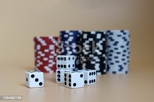 istock Five dice with the pile of casinos chips. 1034062738