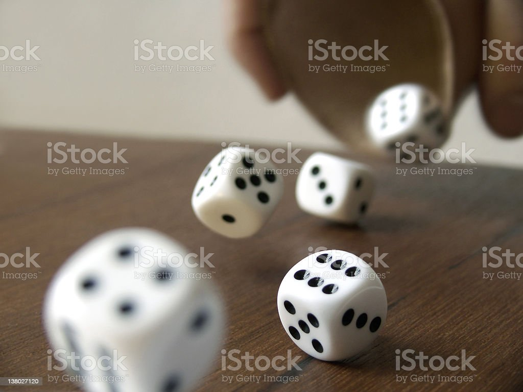 Five dices rolling from a wooden cup on a wooden surface stock photo