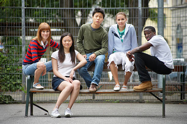 Five diverse young people sitting on a bench  teenagers only stock pictures, royalty-free photos & images