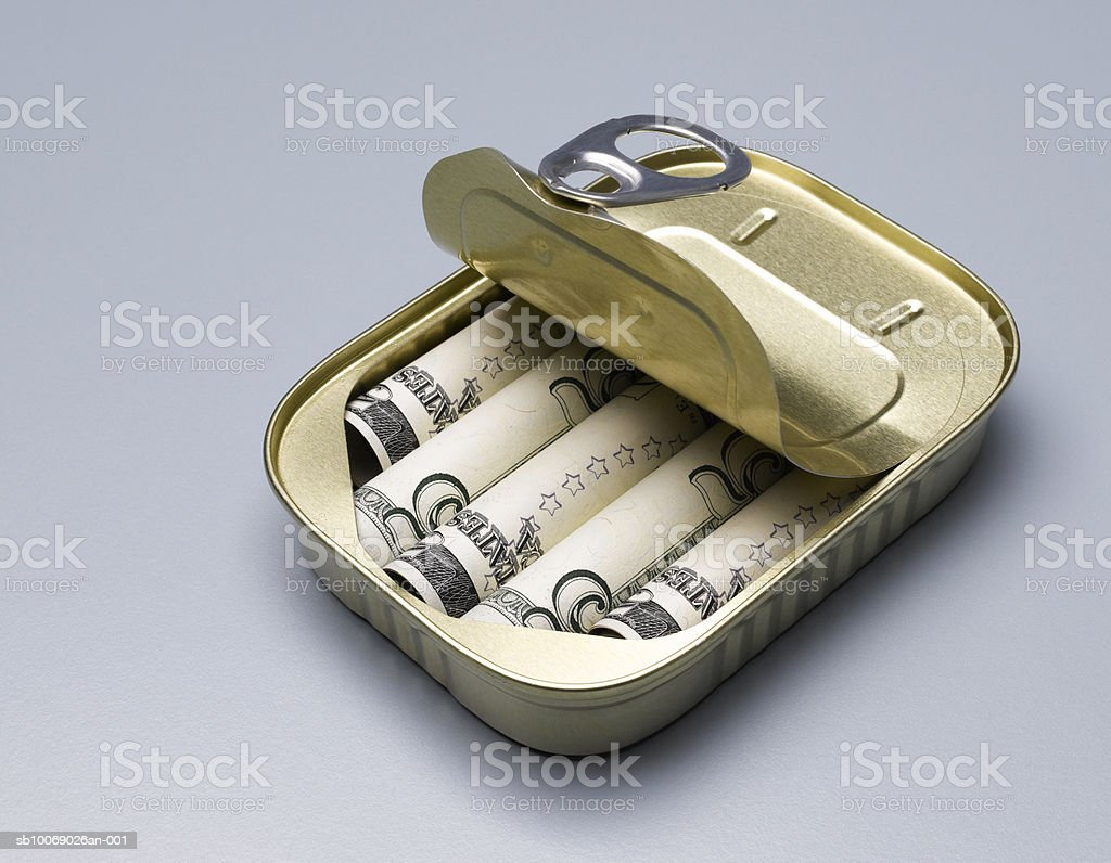 Five dollar bills in sardine can with open lid, studio shot royalty-free stock photo