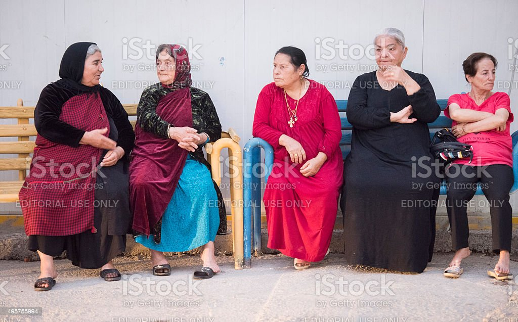 Five elderly ladies sitting on bench stock photo