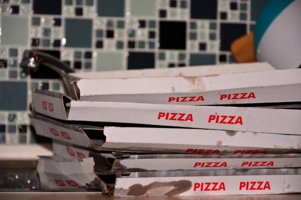 vijf lege dirty dozen van pizza liggen op de keukentafel. - dikke pizza close up stockfoto's en -beelden