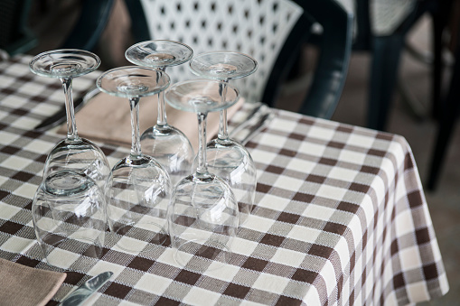five empty wine glasses upside down on table with grid tablecloth