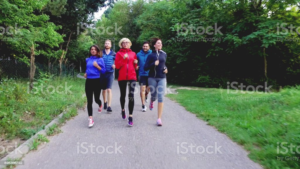 Five energized people running in forest stock photo