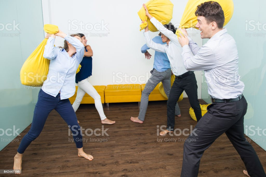 Five Excited People Fighting With Pillows стоковое фото
