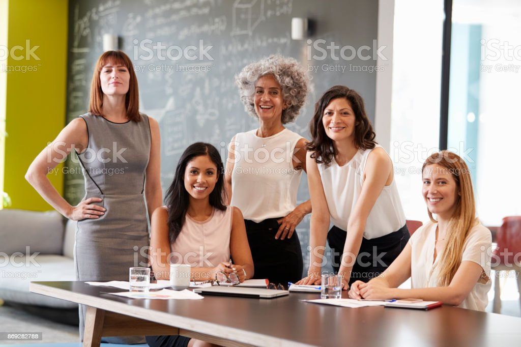 Five female colleagues at a work meeting smiling to camera royalty-free stock photo