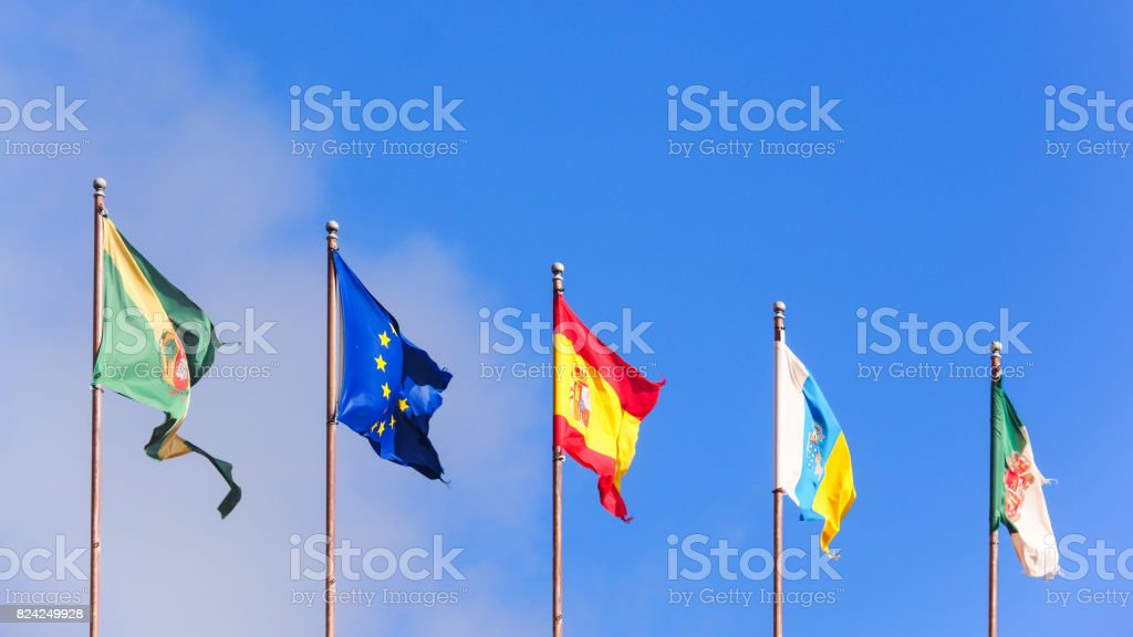 Five flags of different countries isolated on blue sky stock photo