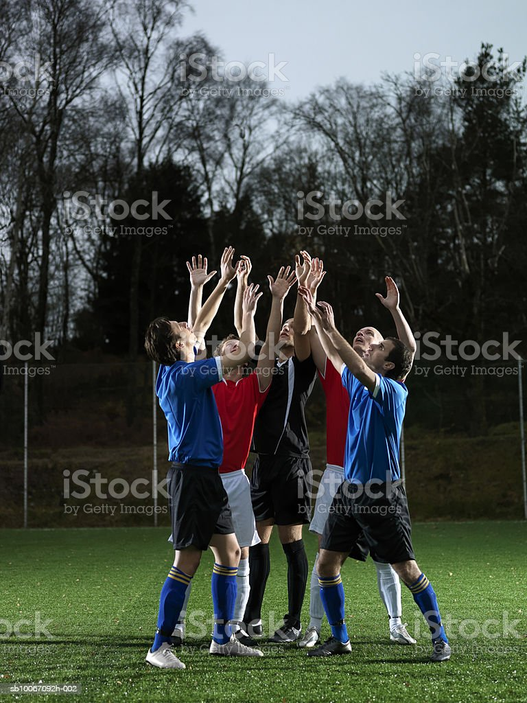 Five football players at pitch, hands raised royalty-free 스톡 사진