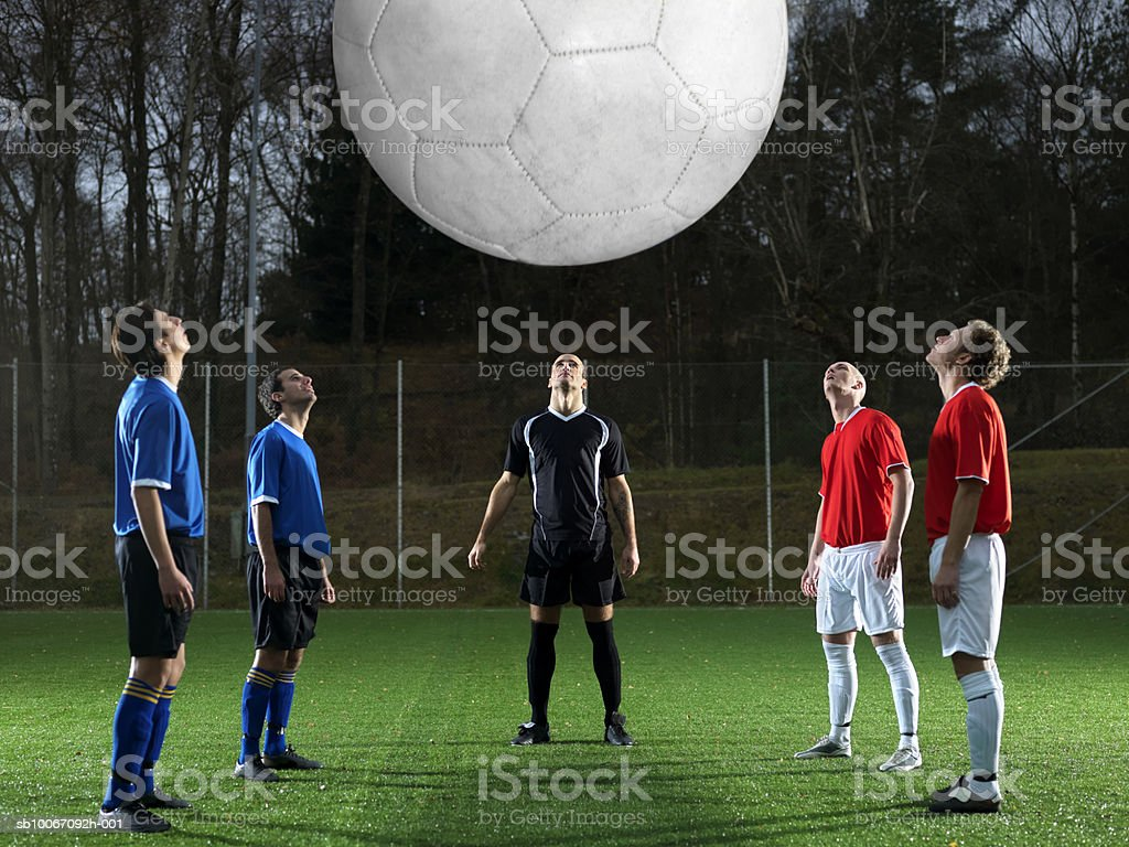 Five football players watching oversized ball royalty-free stock photo