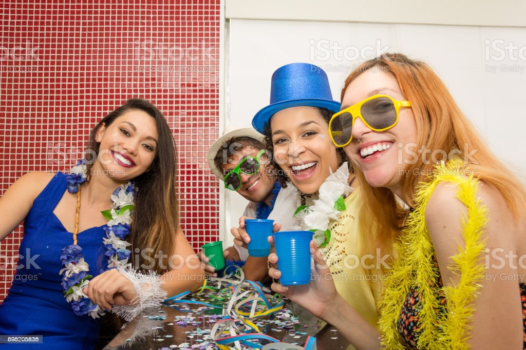 Five friends are dressed up to enjoy the Carnaval. People are laughing and having fun.'n stock photo